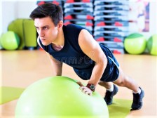 GUY IN GREEN TOP FIT BALL DREAMSTIME