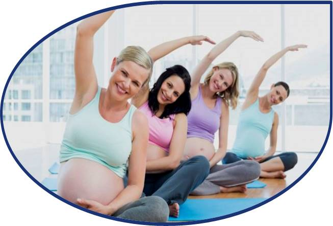 A group of expectant mothers practising stretching in a Yoga class.